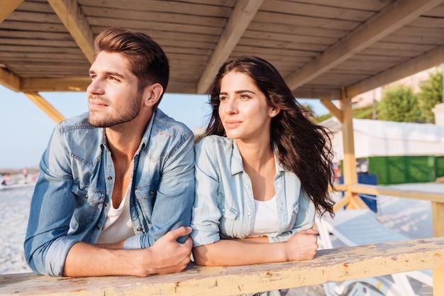 Jovem casal lindo e terno olhando para o mar em pé na casa de praia de madeira