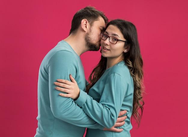 Jovem casal lindo em roupas casuais azuis, homem e mulher, abraçando um homem beijando sua namorada feliz em pé sobre a parede rosa
