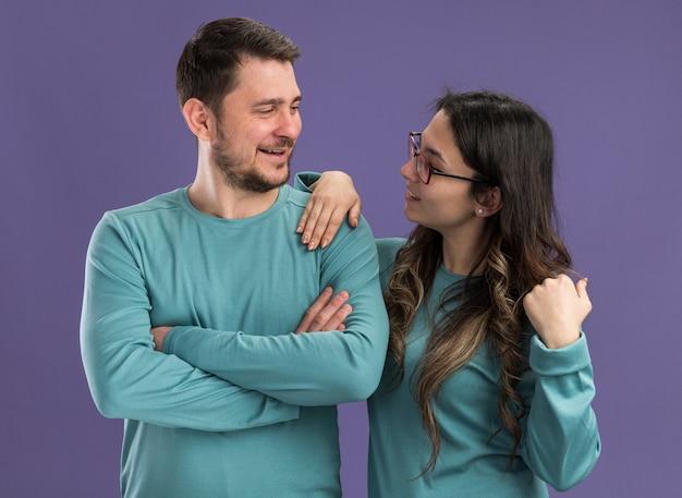 Jovem casal lindo em roupas casuais azuis, homem e mulher olhando um para o outro, felizes e apaixonados em pé sobre a parede roxa