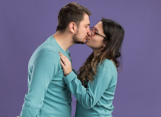 Jovem casal lindo em roupas casuais azuis, homem e mulher se beijando, felizes e apaixonados, em pé sobre a parede roxa