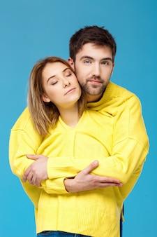 Jovem casal lindo em uma camisola amarela abraçando sorrindo sobre parede azul