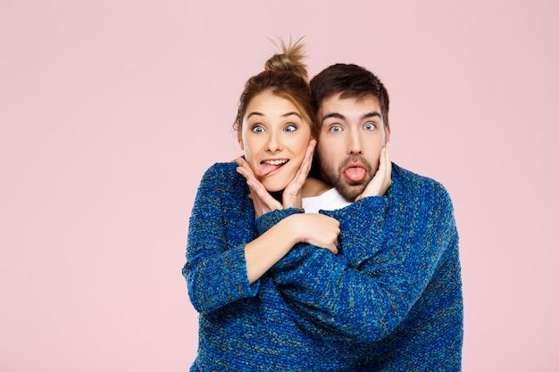 Jovem casal lindo em uma camisola de malha azul posando sorrindo se divertindo sobre parede rosa clara