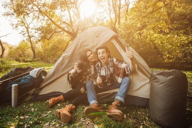 Jovem casal lindo em vestido casual sentado em uma barraca na floresta