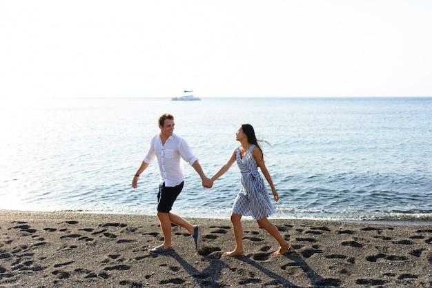 Jovem casal lindo está andando no fundo do mar. filmado na praia de santorini.