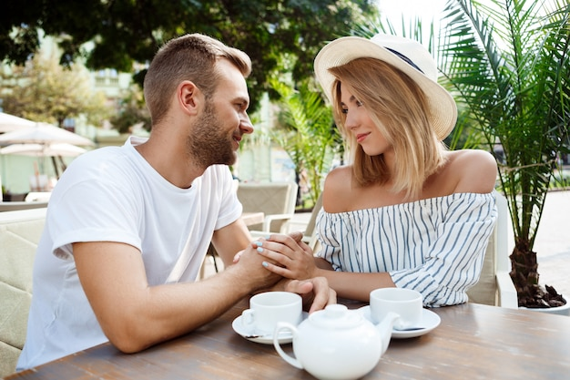 Jovem casal lindo falando, sorrindo, descansando no café.