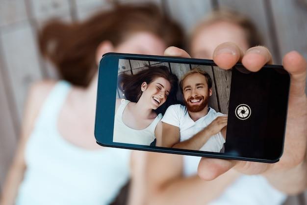Jovem casal lindo fazendo selfie, sorrindo, deitado sobre tábuas de madeira, mostrando a tela do telefone