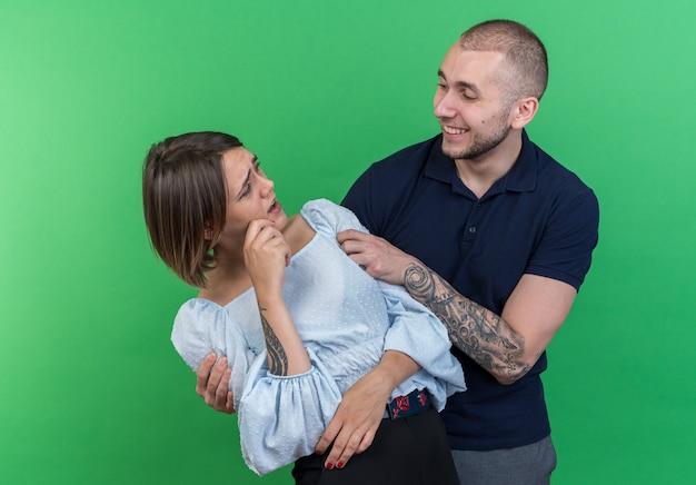 Jovem casal lindo feliz abraçando sua namorada surpresa e confusa em pé