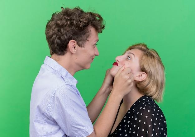 Jovem casal lindo feliz beliscando as bochechas da namorada em pé sobre a parede verde