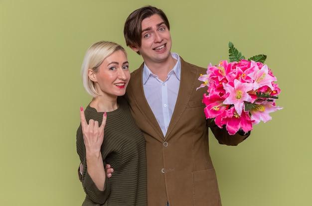 Jovem casal lindo feliz com buquê de flores e uma mulher sorridente