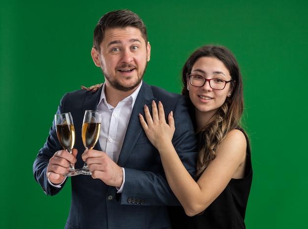 Jovem casal lindo feliz com taças de champanhe e uma mulher sorridente, abraçando-se felizes e apaixonados, celebrando o dia dos namorados em pé sobre a parede verde