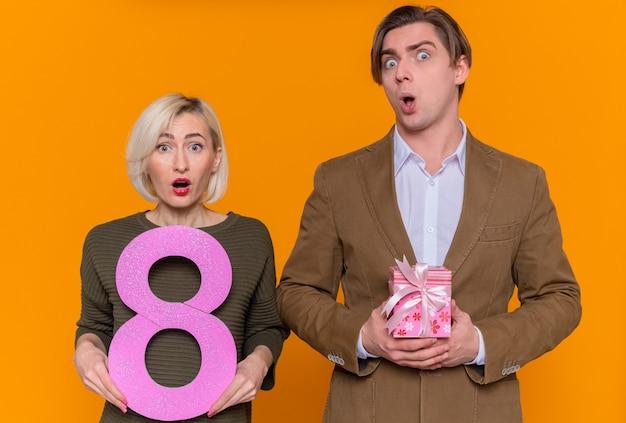 Jovem casal lindo feliz com um presente e uma mulher segurando o número oito