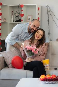 Jovem casal lindo feliz dando um buquê de flores para sua namorada sorridente, sentado em um sofá em uma sala iluminada, comemorando o dia internacional da mulher