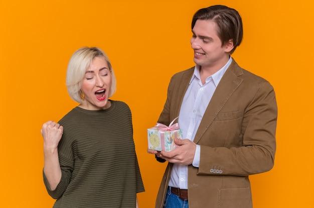Jovem casal lindo feliz dando um presente para sua adorável namorada animada
