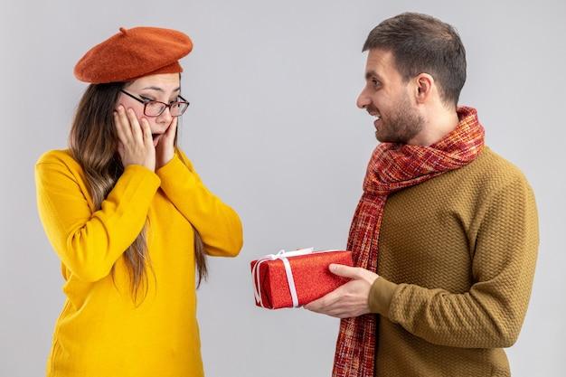 Jovem casal lindo feliz dando um presente para sua namorada sorridente e surpresa na boina feliz apaixonado juntos comemorando o dia dos namorados em pé sobre um fundo branco