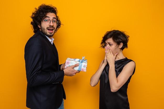 Jovem casal lindo feliz dando um presente para sua namorada surpresa e espantada, comemorando o dia internacional da mulher, 8 de março, em pé sobre um fundo laranja
