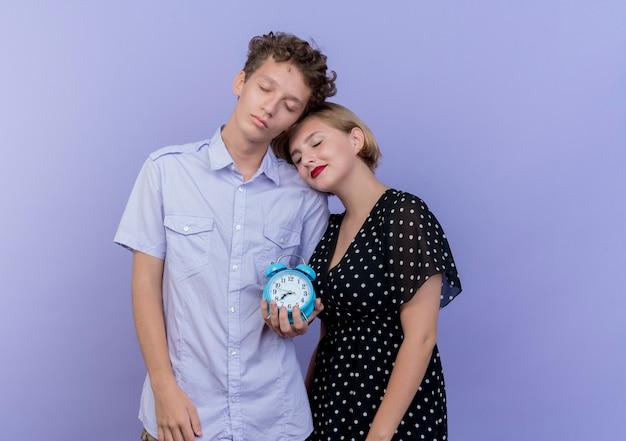 Jovem casal lindo feliz e apaixonado segurando o despertador sobre o azul