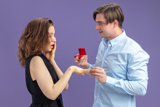 Jovem casal lindo feliz fazendo uma proposta com anel de noivado em uma caixa vermelha para sua adorável namorada surpresa durante o dia dos namorados em pé sobre um fundo azul