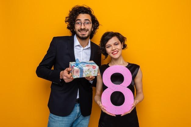 Jovem casal lindo feliz homem com presente e mulher com número oito olhando para a câmera sorrindo alegremente, comemorando o dia internacional da mulher, 8 de março, em pé sobre um fundo laranja