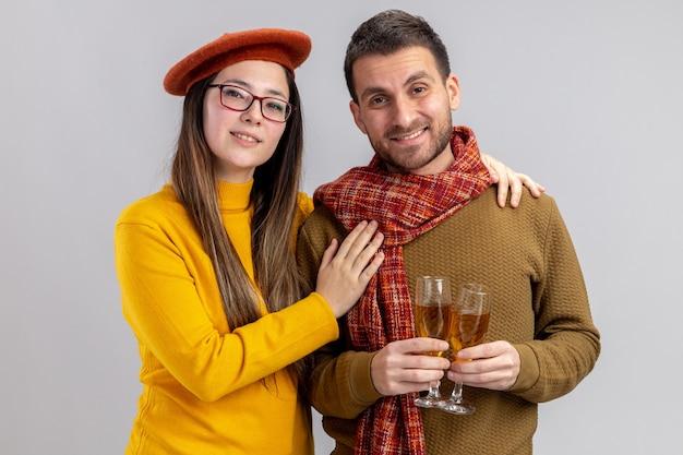 Jovem casal lindo feliz homem e mulher sorridente na boina com copos de champanhe sorrindo alegremente feliz no amor juntos comemorando o dia dos namorados em pé sobre a parede branca