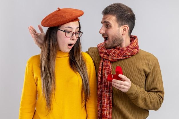 Jovem casal lindo feliz homem fazendo proposta com anel de noivado em caixa vermelha para sua namorada surpresa de boina durante o dia dos namorados em pé sobre uma parede branca