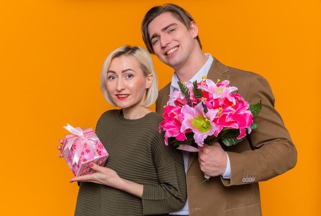 Jovem casal lindo feliz segurando um buquê de flores e uma mulher com um presente feliz e apaixonado, celebrando o dia internacional da mulher em pé sobre a parede laranja