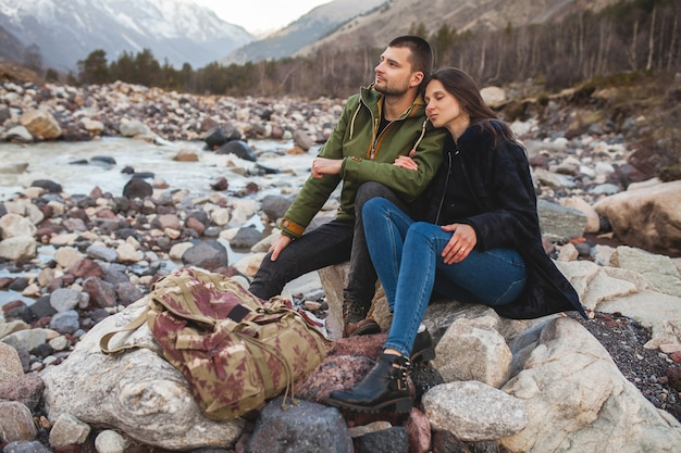 Jovem casal lindo hippie apaixonado, caminhando à beira do rio, natureza selvagem, férias de inverno