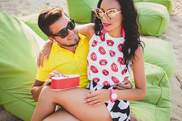 Jovem casal lindo hippie apaixonado, sentado na praia, ouvindo música, óculos de sol, roupa elegante, férias de verão, colorido, emoção positiva