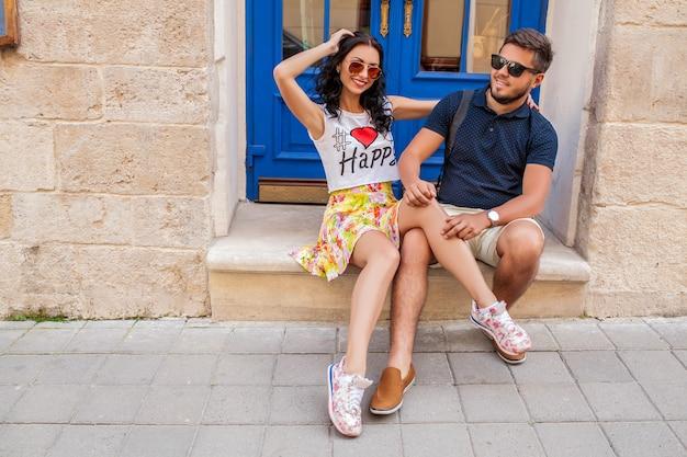 Jovem casal lindo hippie apaixonado, sentado na rua da cidade velha