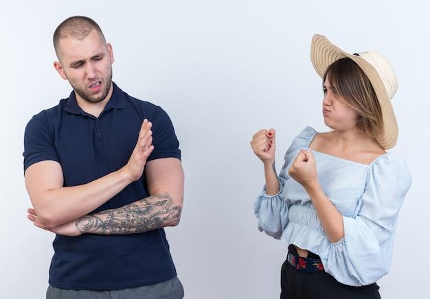 Jovem casal lindo homem e mulher brigando com mulher brava com os punhos cerrados, olhando para o namorado que faz gesto de pare com a mão em pé