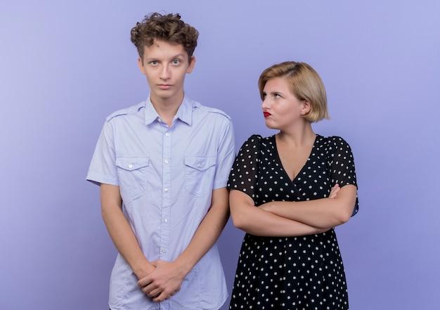 Jovem casal lindo homem e mulher brigando com mulher brava olhando para o namorado descontente em pé sobre a parede azul