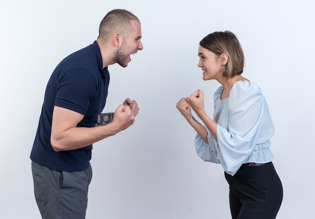 Jovem casal lindo homem e mulher brigando e gritando com os punhos cerrados em pé sobre uma parede branca