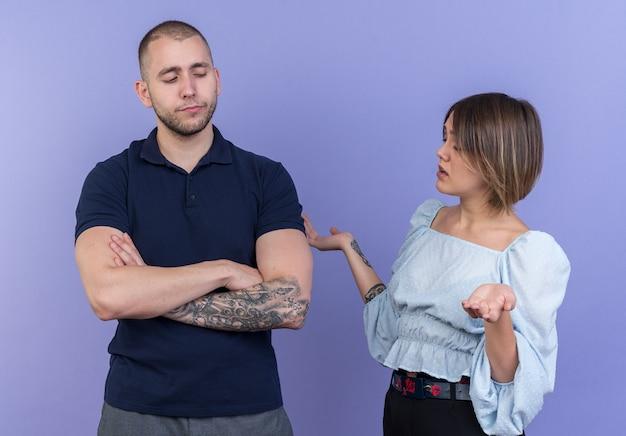 Jovem casal lindo homem e mulher brigando mulher descontente olhando para o namorado ofendido com os braços cruzados em pé