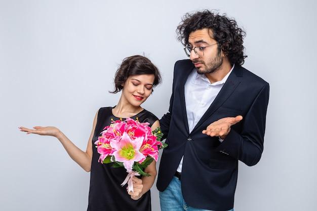 Jovem casal lindo homem e mulher com buquê de flores, parecendo confuso, levantando os braços para celebrar o dia dos namorados