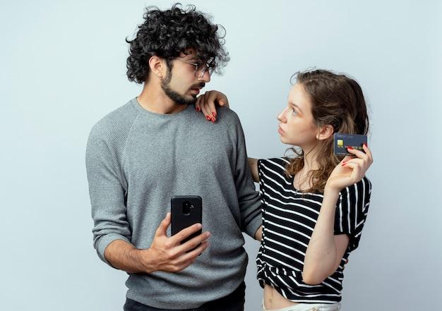 Jovem casal lindo homem e mulher confuso, segurando o smartphone e olhando para a namorada dela, que está segurando o cartão de crédito dele sobre fundo branco