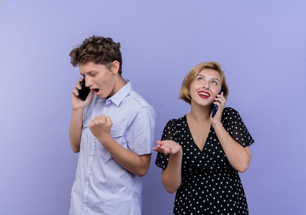 Jovem casal lindo homem e mulher falando no celular, felizes e animados, cerrando os punhos sobre o azul