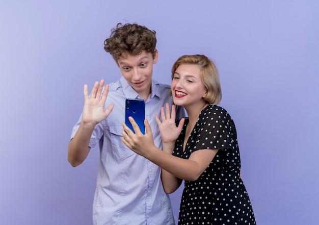 Jovem casal lindo homem e mulher fazendo videochamada, acenando com as mãos e sorrindo sobre o azul