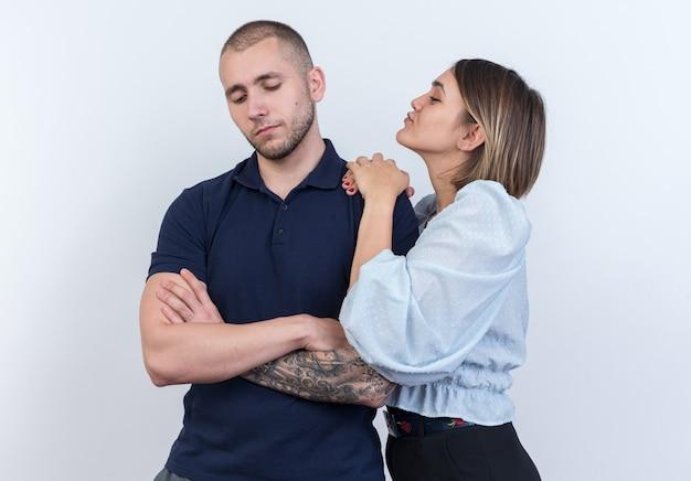 Jovem casal lindo homem e mulher feliz e sorridente, segurando as mãos no ombro do namorado ofendido