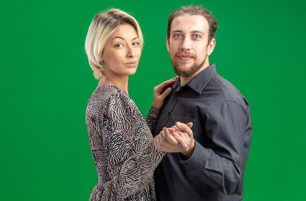 Jovem casal lindo homem e mulher felizes apaixonados juntos dançando celebrando o dia dos namorados em pé sobre fundo verde