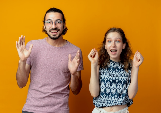 Jovem casal lindo, homem e mulher, felizes e animados, cerrando os punhos e levantando os braços em pé sobre um fundo laranja