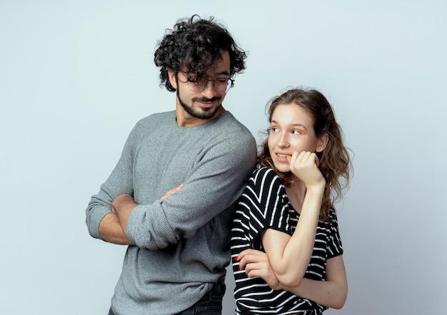 Jovem casal lindo homem e mulher felizes e positivos em pé de costas um para o outro sobre um fundo branco