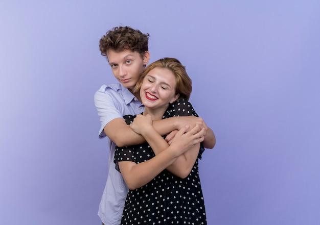 Jovem casal lindo homem e mulher juntos, felizes e apaixonados, abraçando-se sobre uma parede azul