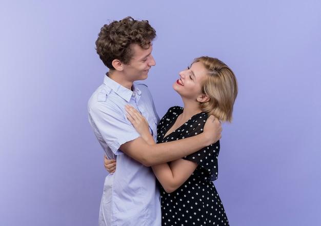 Jovem casal lindo homem e mulher juntos felizes e apaixonados sorrindo sobre o azul
