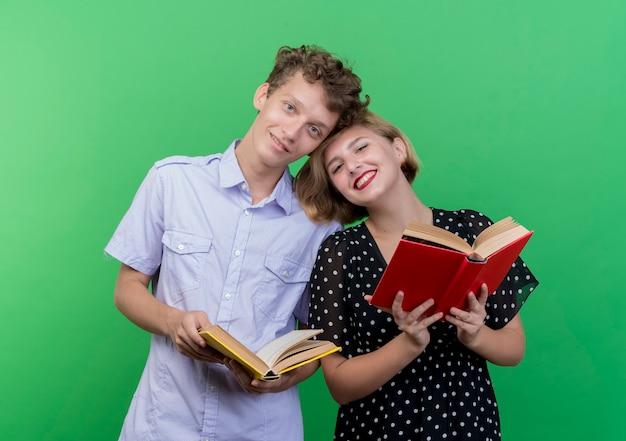 Jovem casal lindo homem e mulher juntos segurando livros, felizes e positivos, sorrindo em pé sobre a parede verde