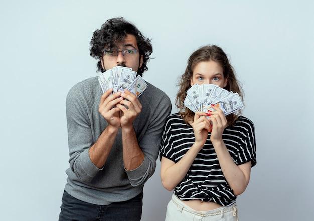 Jovem casal lindo, homem e mulher, mostrando dinheiro, feliz e animado, olhando para a câmera sobre fundo branco