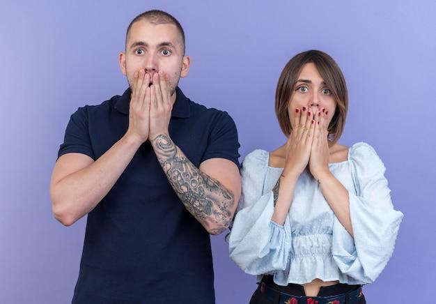 Jovem casal lindo homem e mulher olhando em choque cobrindo a boca com as mãos em pé