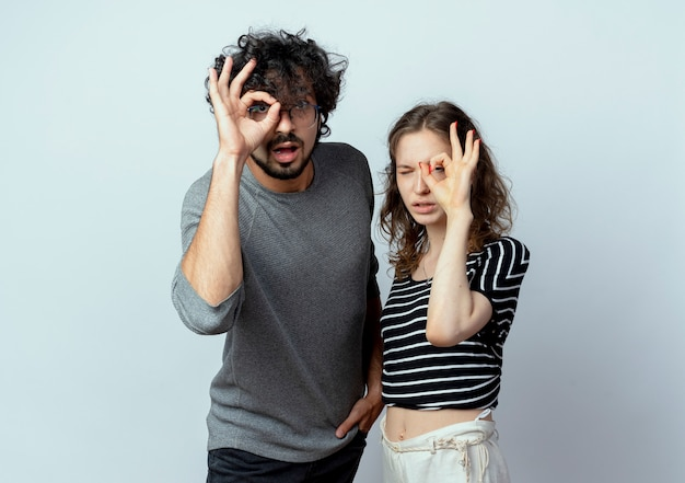 Jovem casal lindo homem e mulher olhando para a câmera fazendo sinal de ok em pé sobre fundo branco