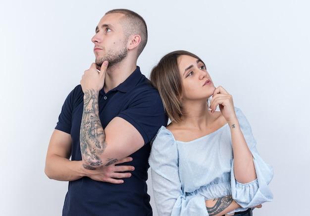 Jovem casal lindo homem e mulher olhando para o lado com expressão pensativa e pensando em pé, costas com costas