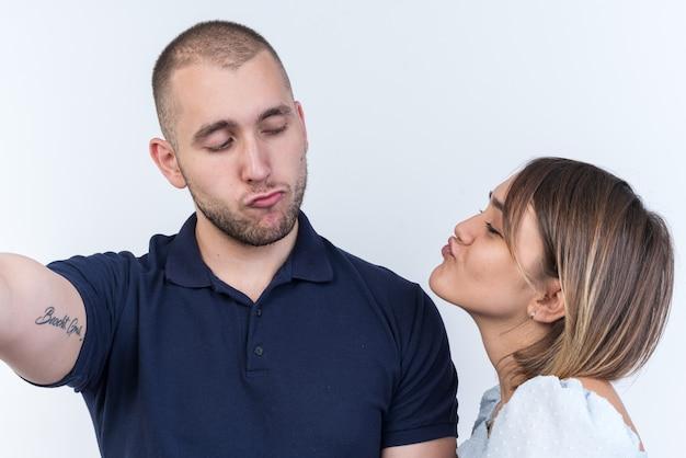 Jovem casal lindo homem e mulher olhando um para o outro, felizes e apaixonados, vão se beijar em pé sobre uma parede branca