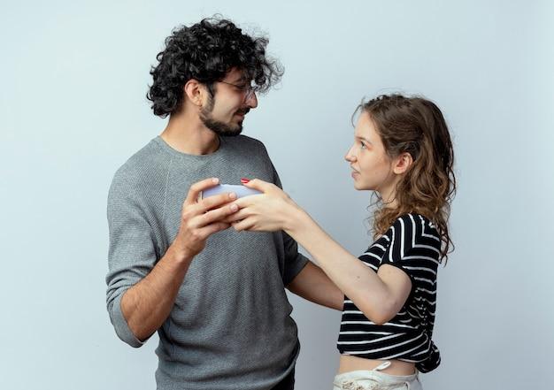 Jovem casal lindo homem e mulher olhando um para o outro segurando um smartphone, tirando uma foto deles juntos em pé sobre um fundo branco