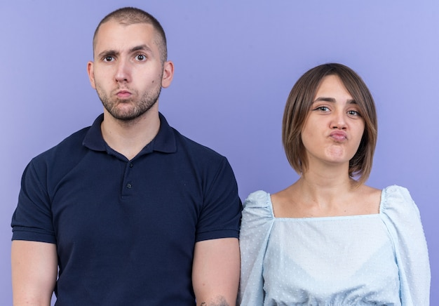 Jovem casal lindo homem e mulher parecendo confuso e muito ansioso em pé